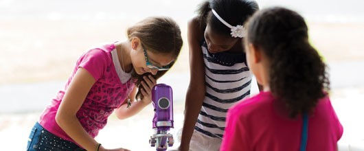 Girl Scouts looking at a microscope